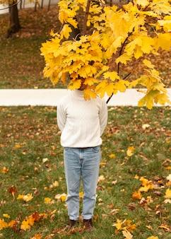 Jeune homme derrière les feuilles d'automne