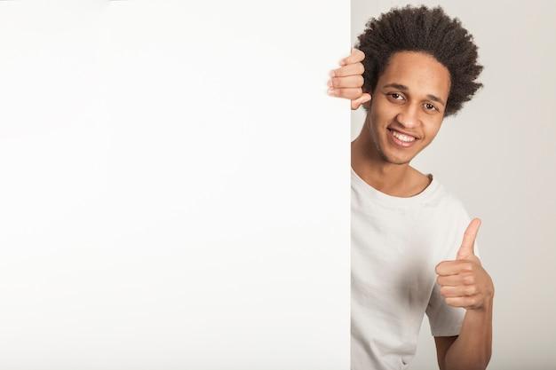 Jeune homme derrière la porte faisant signe ok