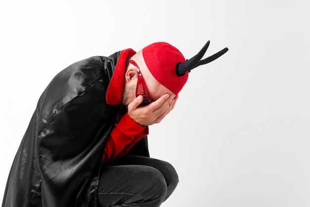 Jeune homme désespéré en vêtements de mascarade et chapeau rouge avec des cornes noires couvrant son visage avec la main