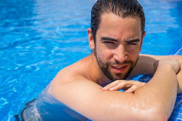 Jeune homme détendu dans la piscine