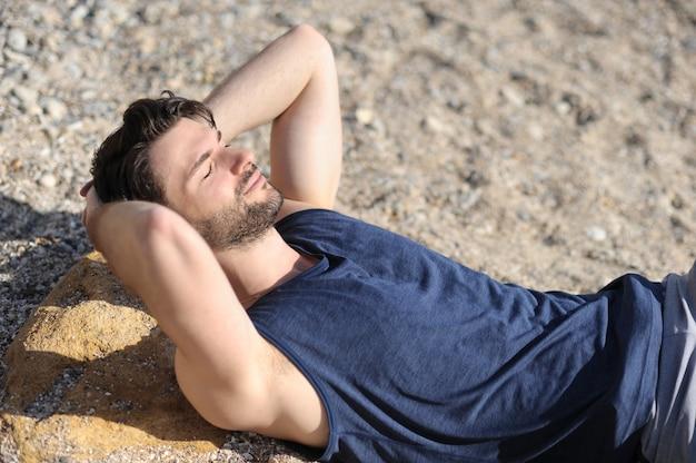 Jeune homme détendu portrait en plein air, allongé sur un sable