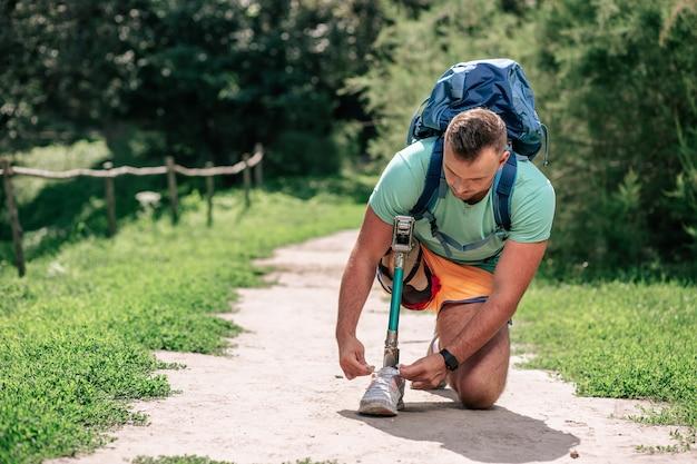 Jeune homme déterminé avec une prothèse attachant ses chaussures tout en ouvrant de nouvelles voies à l'extérieur