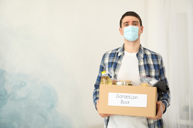 Jeune homme détient une boîte de dons. bénévole. covid 19