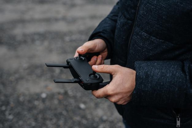 Un jeune homme détient une télécommande pour contrôler un hélicoptère.