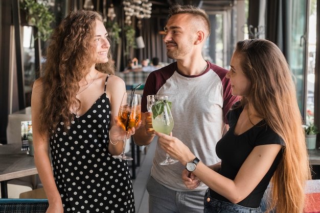 Jeune homme avec deux amies grillant des boissons