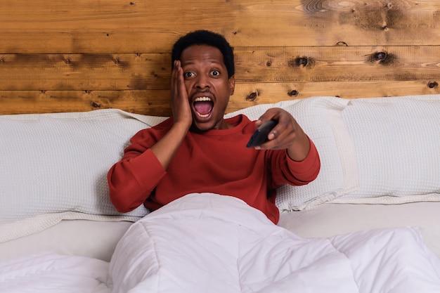 Jeune homme devant la télé sur son lit à la maison.