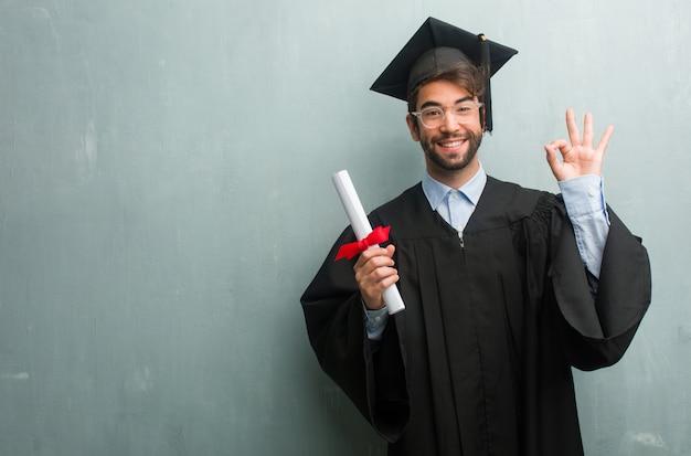 Jeune homme diplômé contre un mur de grunge avec un espace de copie gai et confiant faisant geste ok