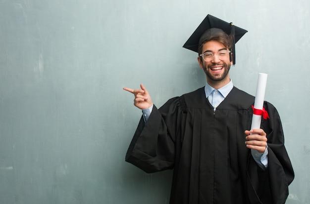 Jeune homme diplômé contre un mur de grunge avec un espace de copie pointant vers le côté