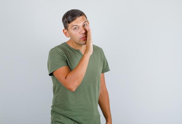 Jeune homme disant quelque chose de confidentiel en t-shirt vert armée, vue de face.