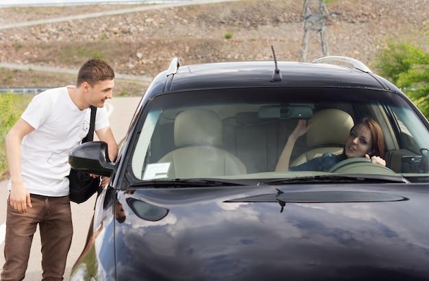 Jeune homme discutant d'une conductrice