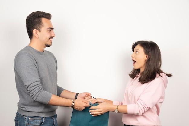 Jeune homme donnant un cadeau à sa petite amie.