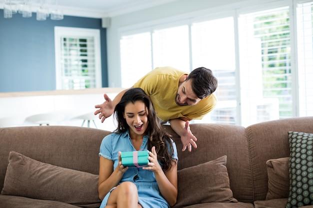 Jeune homme donnant un cadeau surprise à la femme dans le salon à la maison
