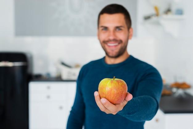 Jeune homme donnant à la caméra des fruits sains