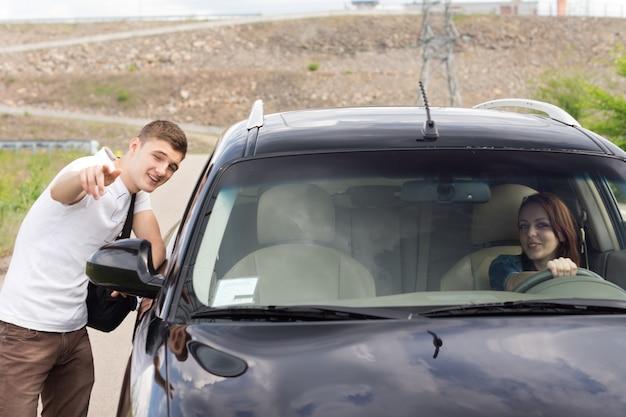 Jeune homme donnant des instructions à une femme conductrice