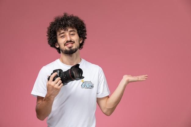 Jeune homme donnant la main vide avec sa photocamera