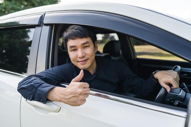 Jeune homme donnant le pouce à l'intérieur de sa voiture