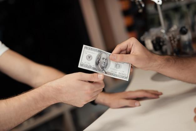 Un jeune homme donne de l'argent à un autre homme.