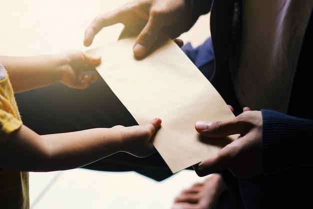 Un jeune homme donne une enveloppe à une petite fille