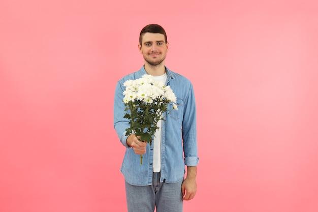 Jeune homme donne des fleurs sur fond rose.