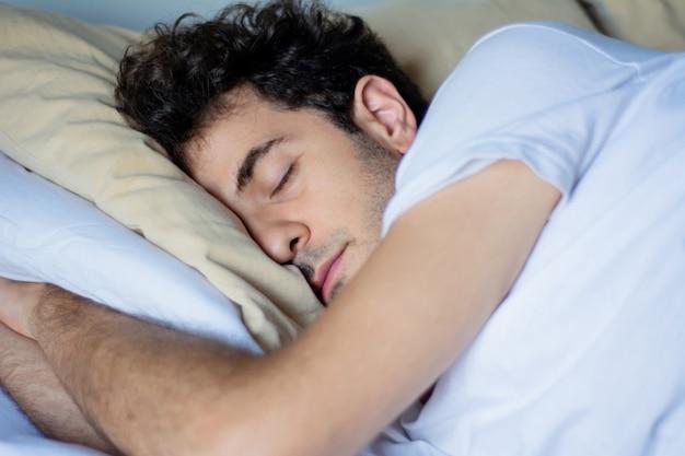 Jeune homme dort dans lit