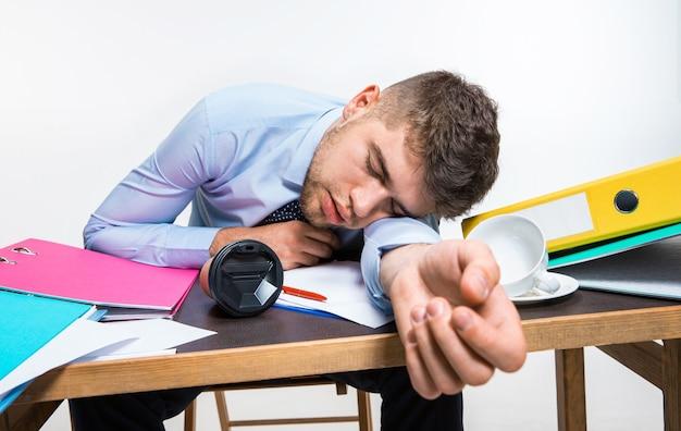 Le jeune homme dort effrontément sur le bureau pendant ses heures de travail
