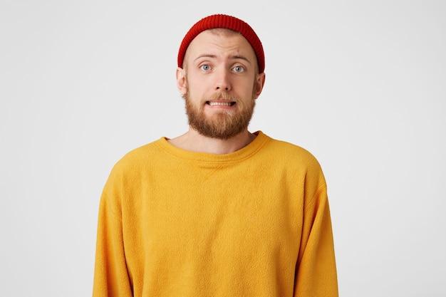 Un jeune homme douteux avec une barbe rousse est très nerveux