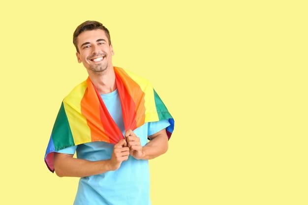 Jeune homme avec drapeau lgbt sur la couleur