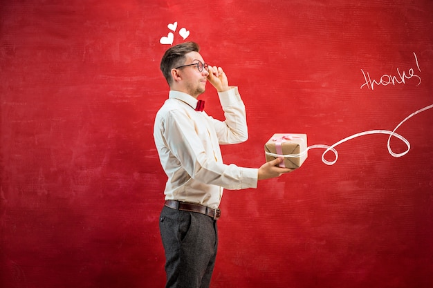 Jeune homme drôle avec cadeau sur fond de studio rouge. le concept de la saint-valentin heureuse