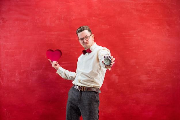 Jeune homme drôle avec coeur abstrait et horloge