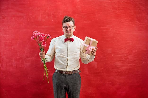 Jeune homme drôle déçu avec des fleurs et des cadeaux sur studio rouge
