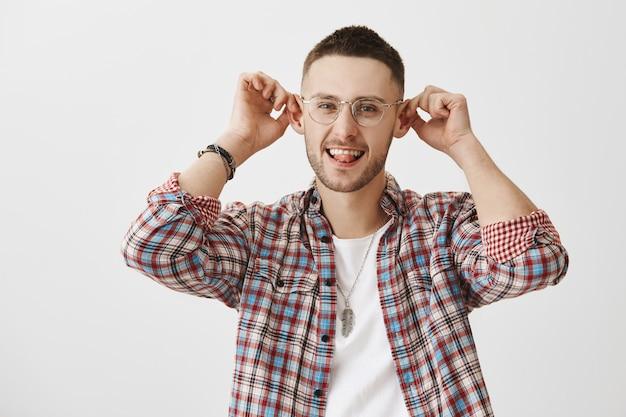 Jeune homme drôle et idiot avec des lunettes posant