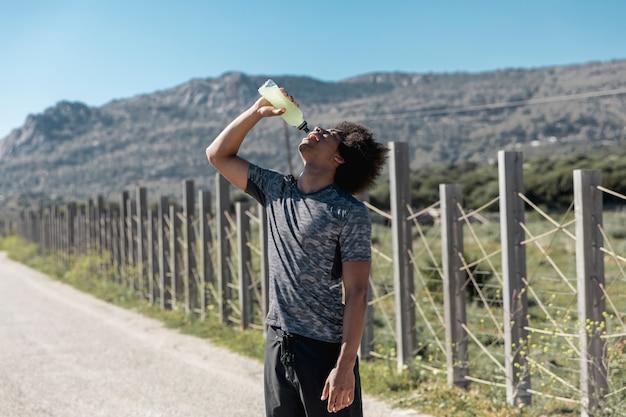 Jeune homme, eau potable, sur, route