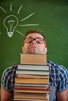 Jeune homme échevelé tenant une pile de livres.