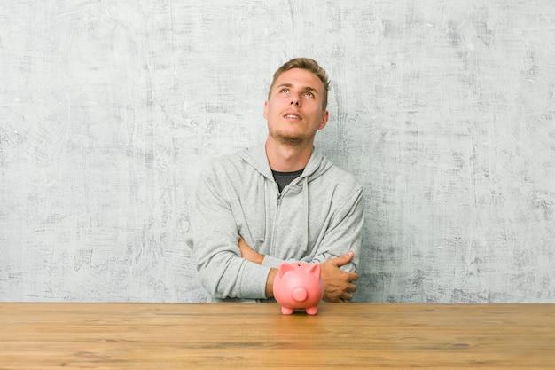 Jeune homme, économiser de l'argent avec une tirelire fatigué d'une tâche répétitive