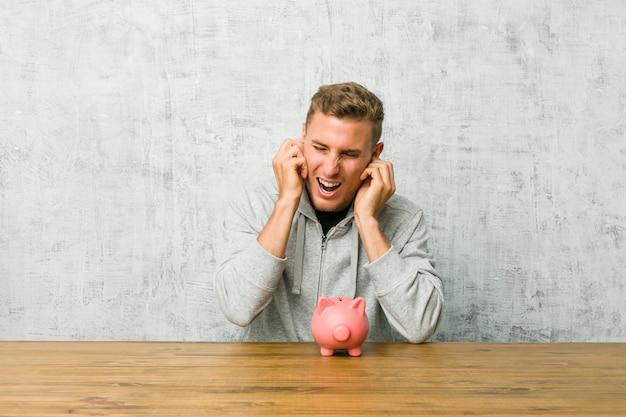 Jeune homme, économiser de l'argent avec une tirelire qui couvre les oreilles avec les mains.