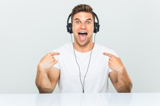 Jeune homme écoutant de la musique avec des écouteurs surpris se montrant du doigt, souriant largement.