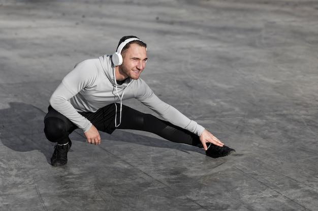 Jeune homme écoutant de la musique et faisant des exercices d'échauffement