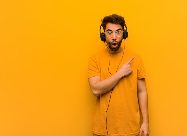 Jeune homme écoutant de la musique pointant vers le côté