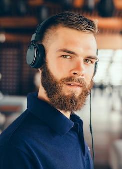Jeune homme écoute de la musique au casque, à l'aide de smartphone, portrait de hipster en plein air