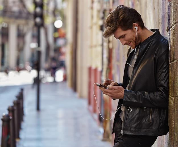 Jeune homme, écoute, musique, écouteurs smartphone