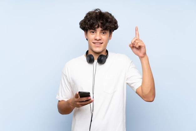 Jeune homme écoute de la musique avec un téléphone portable sur un mur bleu isolé pointant vers le haut une excellente idée
