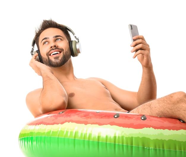 Jeune homme avec des écouteurs, anneau gonflable et téléphone portable sur blanc