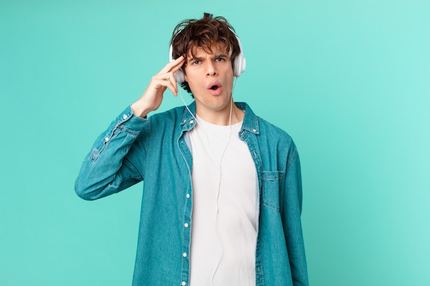 Jeune homme avec des écouteurs ayant l'air surpris, réalisant une nouvelle pensée, idée ou concept