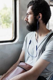 Jeune homme avec des écouteurs dans le train. une brune avec une barbe est assise près de la fenêtre. tourisme et voyages. verticale.