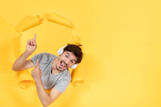 Jeune homme avec des écouteurs pointant au-dessus sur un fond de papier jaune musique ultrasonore audio