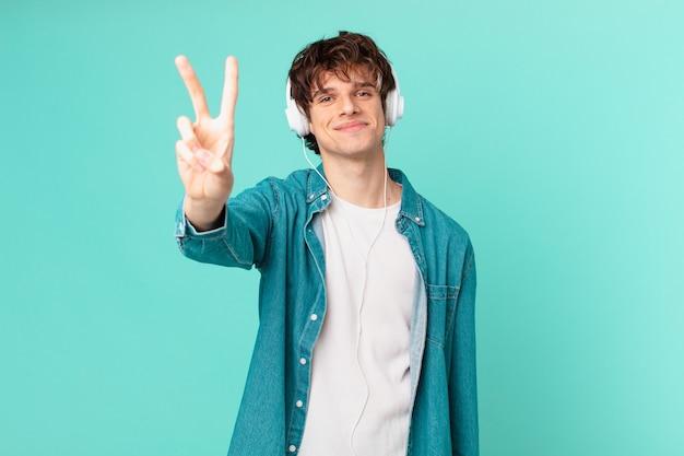 Jeune homme avec des écouteurs souriant et semblant amical, montrant le numéro deux
