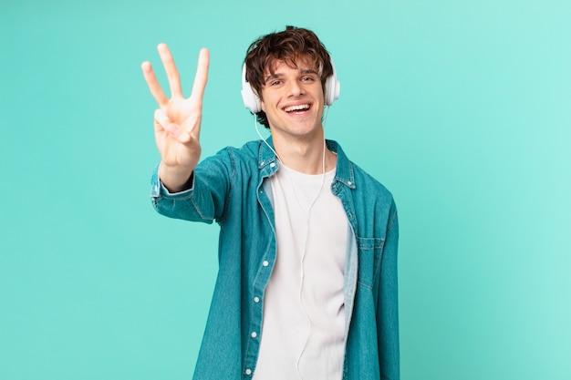 Jeune homme avec des écouteurs souriant et semblant amical, montrant le numéro trois