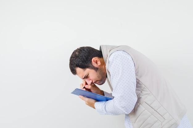 Jeune homme écrivant quelque chose sur un ordinateur portable avec un stylo en veste beige et à la recherche concentrée. vue de face.