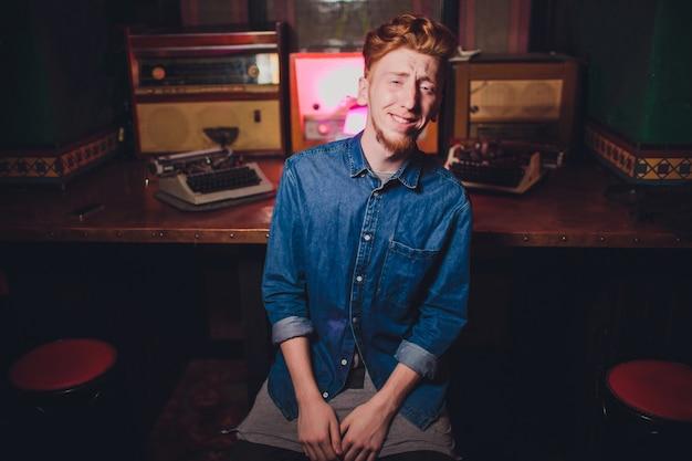 Jeune homme écrivant sur une vieille machine à écrire. dans un éclairage sombre, restaurant, vêtements modernes, vieilles habitudes d'écrivain