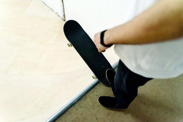Jeune homme effectuant des acrobaties avec un skate indoor.